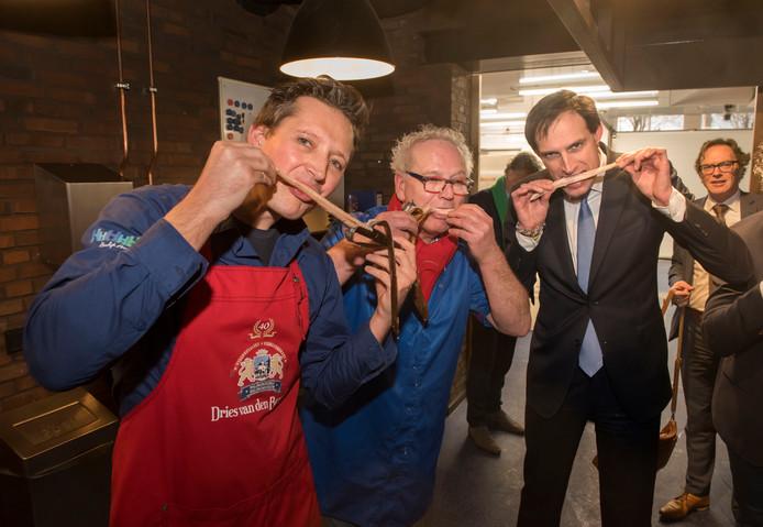 Minister Wopke Hoekstra laat de vers gerookte paling zich goed smaken. Links Peter en Dries van den Berg. Rechts de Harderwijkse CDA-fractievoorzitter Peter Sels.