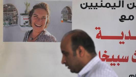 Een journalist in Jemen passeert een poster waarop Spiegel staat afgebeeld tijdens een protest waarbij om de vrijlating van het Nederlandse stel wordt gevraagd.