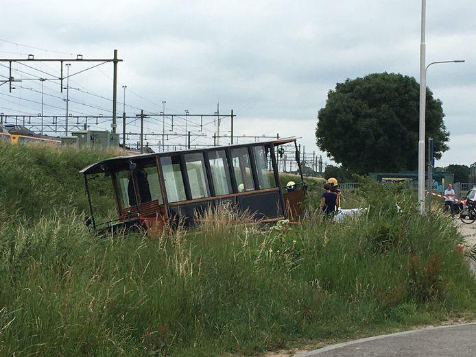 De tram hangt half in de sloot.