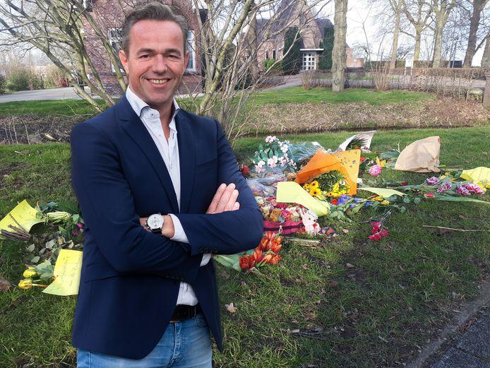 Columnist Dennis Captein. Op de achtergrond de bloemen en briefjes op een grasveld voor begraafplaats Vredehof in Bodegraven.