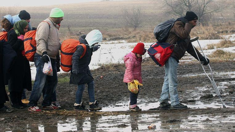 Vluchtelingen ploeteren door de modder op weg naar een tijdelijk opvangkamp in Macedonië. Beeld epa