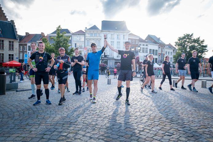 Olivier Verhaege (in het blauw) komt tijdens zijn O-Five run aan op de Grote Markt van Mechelen.