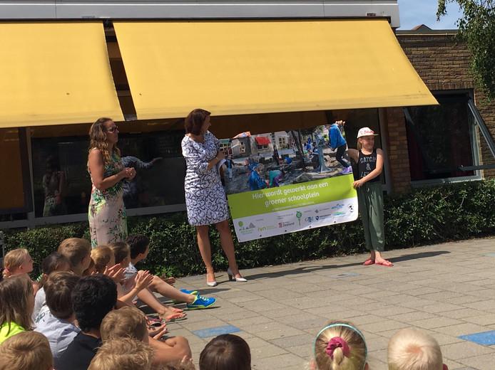 Gedeputeerde Anita Pijpelink (m) en kinderdirecteur groene schoolpleinen Jedithja Steenbeek (r) overhandigen een spandoek aan de Regenboog in Middelburg