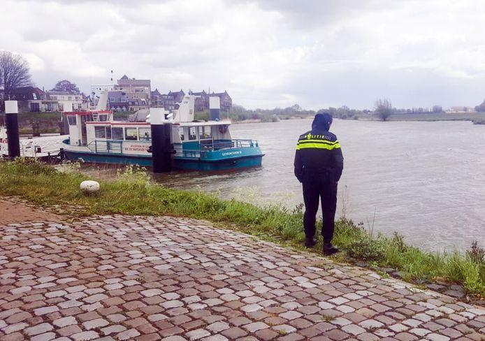 Politieman Mark den Hartog op de plek waar de auto in de Merwede verdween.
