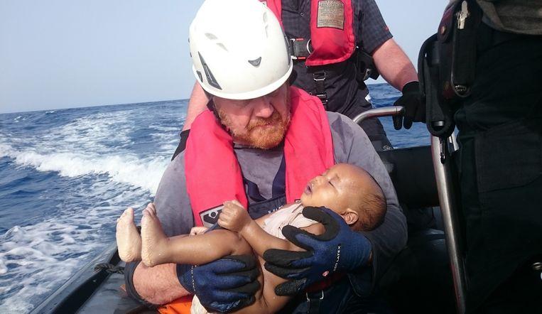 Een Duitse hulpverlener houdt een verdronken baby vast. Beeld ap