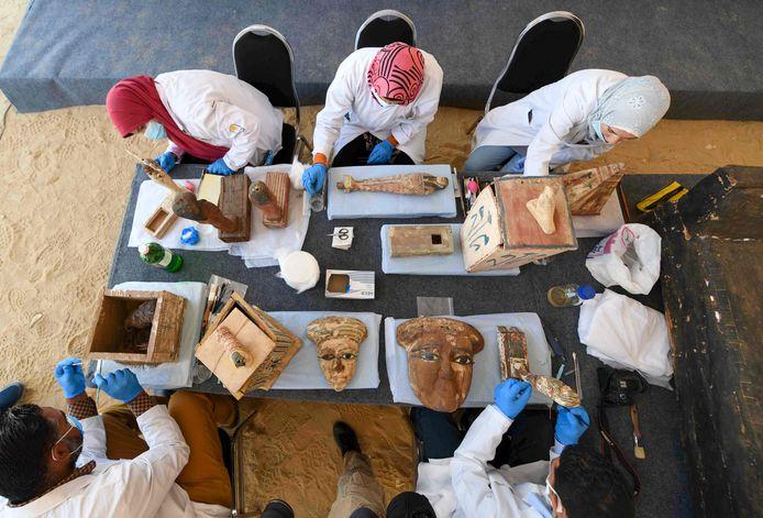 Archeologen maken maskers en standbeelden schoon tijdens de onthulling van de sarcofagen in Sakkara.