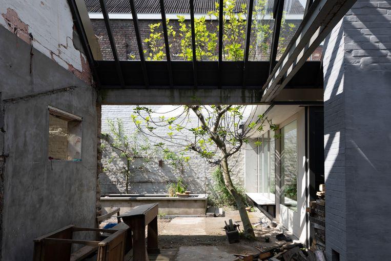 De dakstructuur van de oude achterbouw werd behouden en deels afgewerkt met glas zodat er een orangerie ontstond.   Beeld Faye pynaert