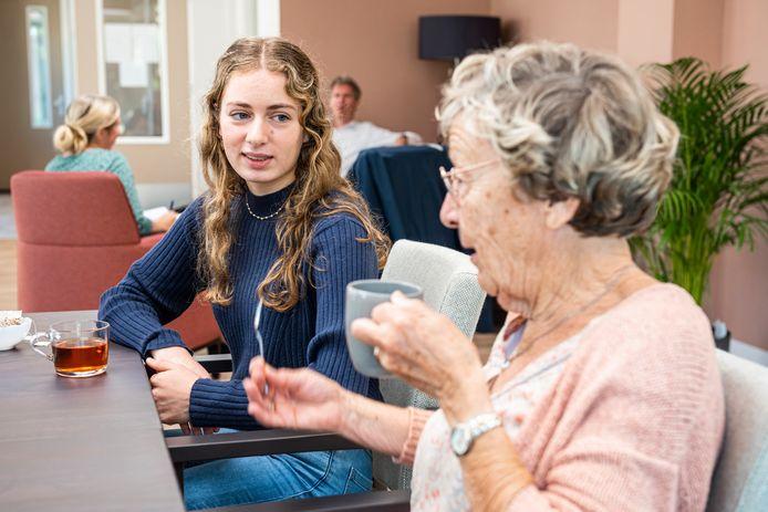 Lonneke praat met een van de senioren waarmee ze samenwoont.