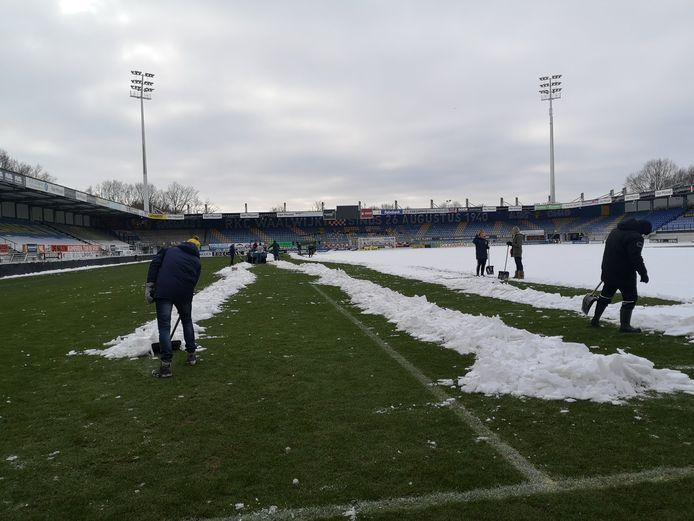 Kantoorpersoneel en directie van RKC Waalwijk zijn druk in de weer om het veld in het Mandemakers Stadion sneeuwvrij te maken.