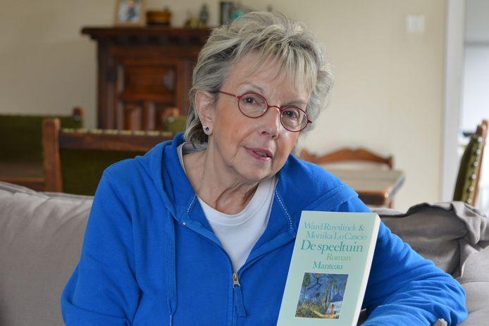 Weduwe Monika met het boek 'De speeltuin' dat ze samen met haar man schreef.
