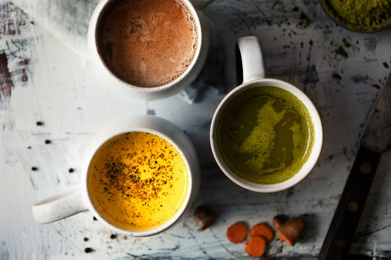 three different types of antioxidant beverages on rustic table, green matcha tea, turmeric milk, chocolate latte. Top down view Beeld Getty Images