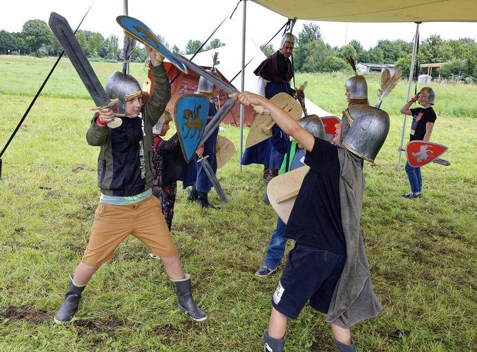 Kinderen krijgen een les zwaardvechten bij het Ridderkamp in Vlijmen.