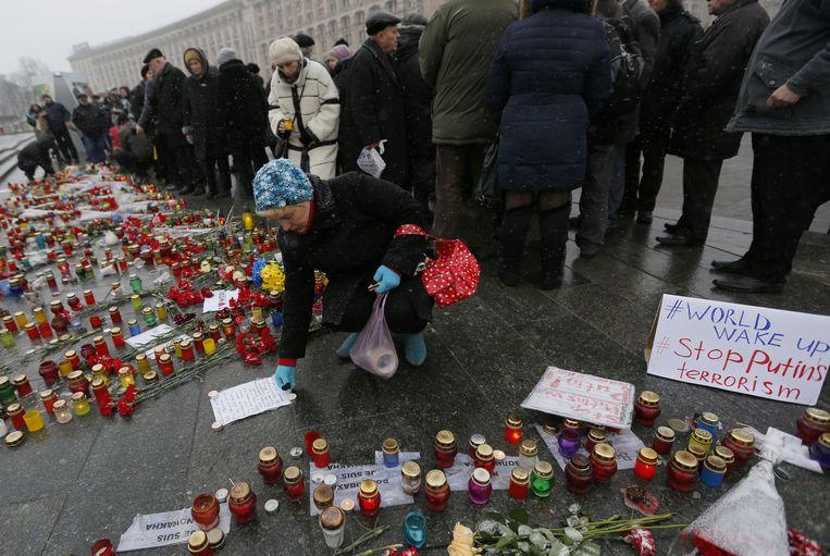 Mensen branden vandaag kaarsen op het Onafhankelijkheidsplein in Kiev voor de slachtoffers van de raketaanval in Marioepol. Beeld AP