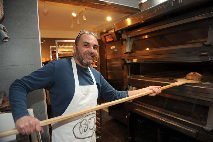 Didier haalt een versgebakken brood uit de oven.