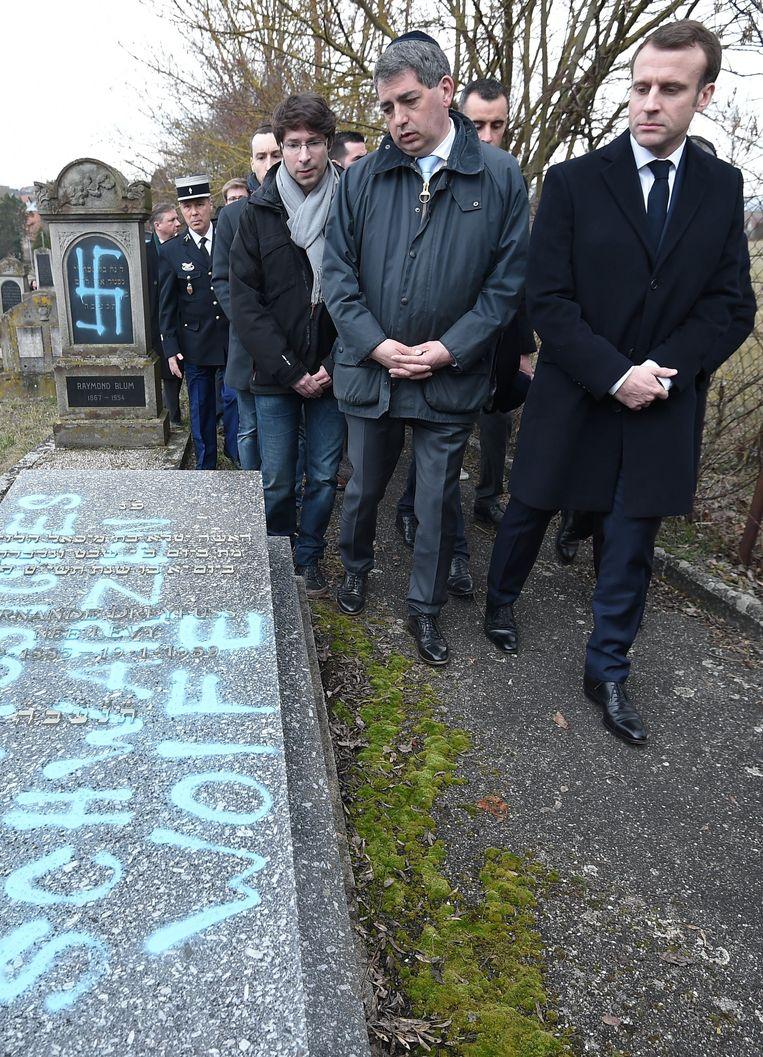 De Franse president Emmanuel Macron bezoekt het gevandaliseerde Joods kerkhof in Quatzenheim. Beeld Photo News