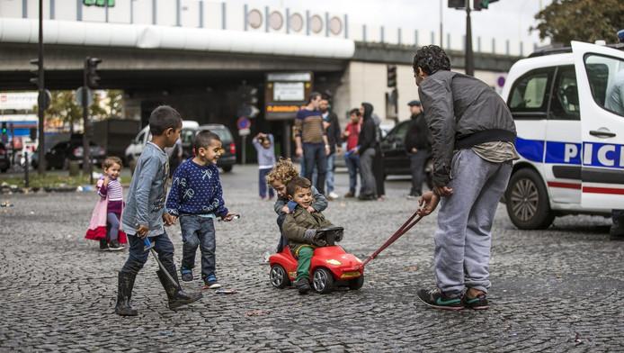 Een Syirische vader speelt met zijn kinderen op straat in het noorden van Parijs.