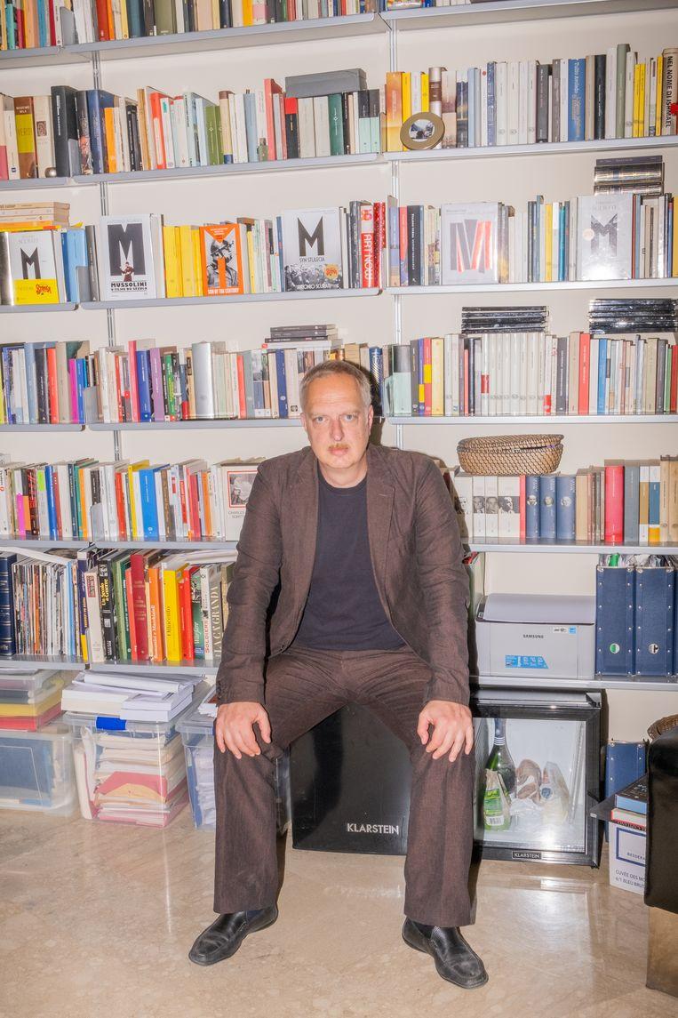 Antonio Scurati voor zijn boekenkast met diverse uitgaven van zijn roman M. Beeld Lucia Buricelli