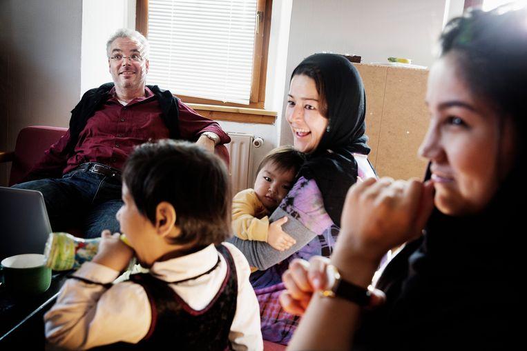De voormalige burgemeester Markus Nierth bezoekt een Afghaans gezin dat mocht verblijven in zijn tweede woonst, in 2015.Het werd hem niet in dank afgenomen in Tröglitz. Beeld Daniel Rosenthal
