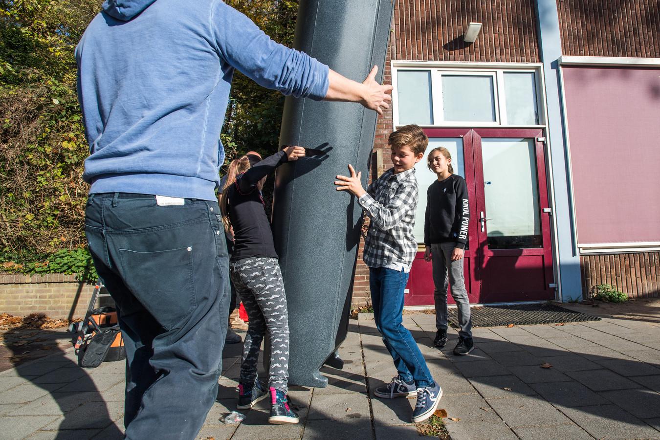 De nieuwe regenton word gemonteerd bij basisschool De Wijzer in Arnhem.