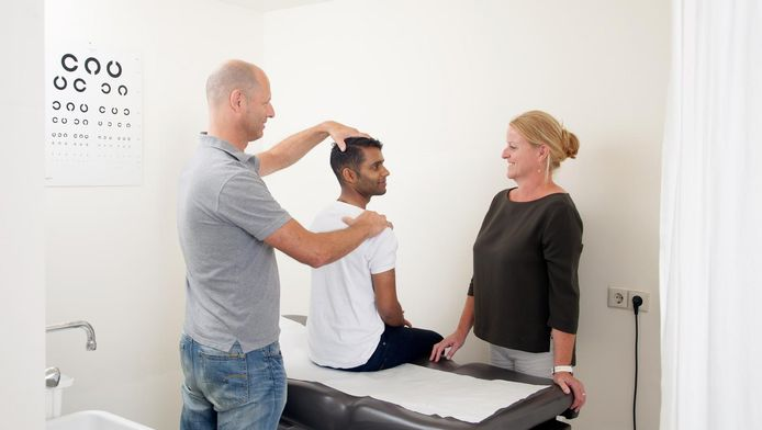 De huisarts (r.) en de fysiotherapeut nemen samen de patiënt onder de loep.