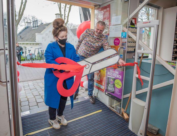 Met het doorknippen van een lint heropende schrijfster Lize Spit woensdag boekwinkel De Koperen Tuin. Eigenaar Anthoni Fierloos hielp haar een handje.