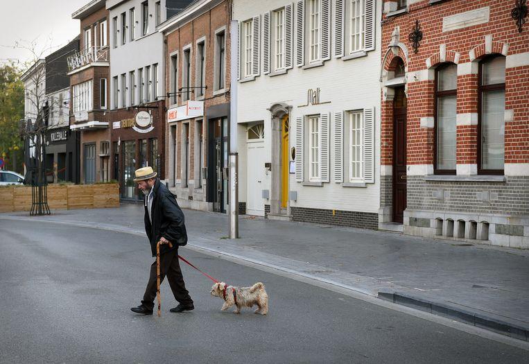 Een man laat zijn hond uit in Ninove. Beeld Marcel van den Bergh