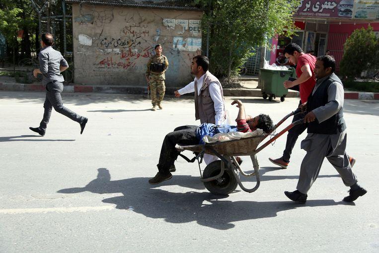Afghaanse mannen dragen gewonden weg van de plaats waar de aanslag heeft plaatsgevonden.  Beeld AP