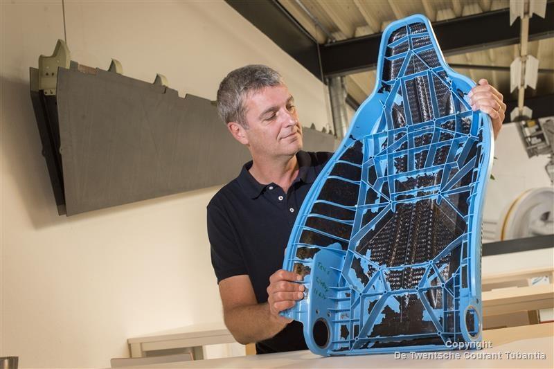 Harald Heerink met een rugleuning van een autostoel gemaakt van thermoplastisch composiet