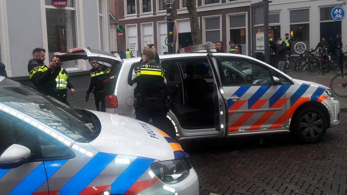 De verdachte die wordt gearresteerd staat ingeklemd tussen de agent en de politieauto.