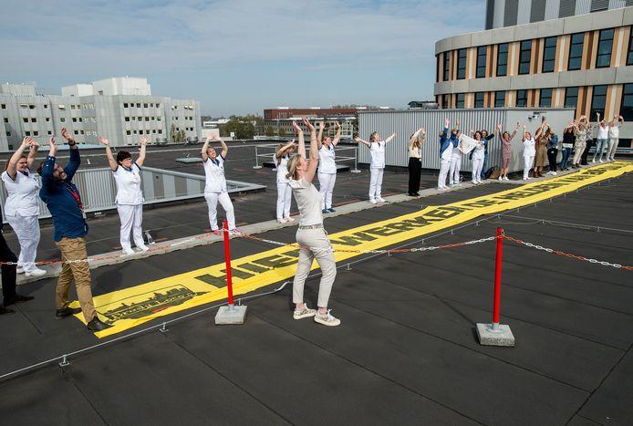 Medewerkers van het Amphia zwaaien op het dak naar de drone.