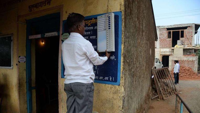 Een verkiezingsmedewerker hangt een uitleg van de stemcomputer op in het dorp Shirgaon, 130 kilometer van Mumbai. Beeld afp