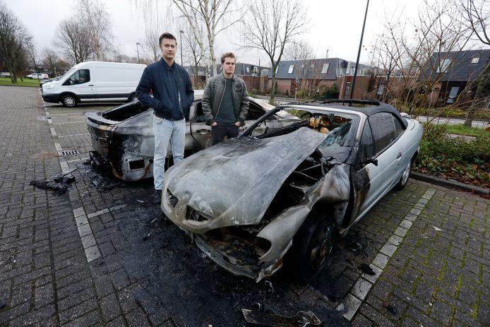 Bob van Houwelingen (links) en Karst Hartman bij hun uitgebrande auto.