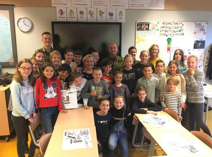 Minister Ank Bijleveld van Defensie omringd door leerlingen van basisschool St. Joseph en hun leerkracht en een aantal militairen.
