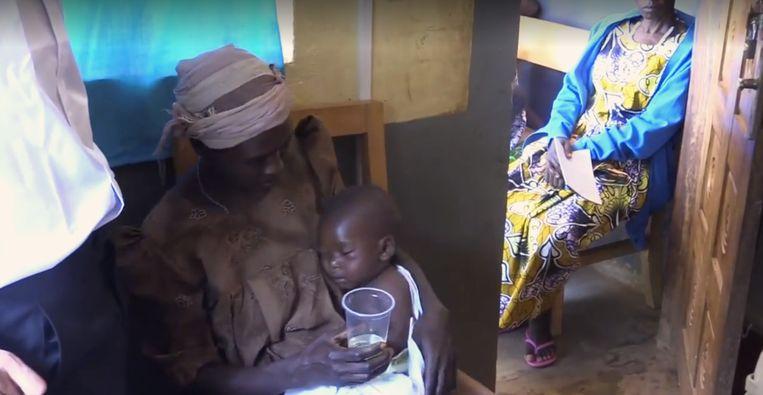 De baby op schoot van zijn moeder krijgt in de video van Sam Little verdund bleekwater te drinken als medicijn tegen malaria.  Beeld Brighteon