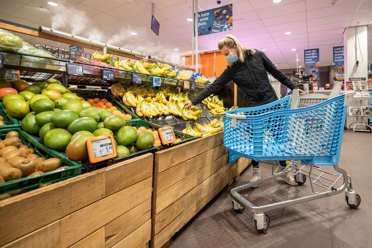 Een klant met mondkapje in een supermarkt van Albert Heijn.   Beeld BSR Agency