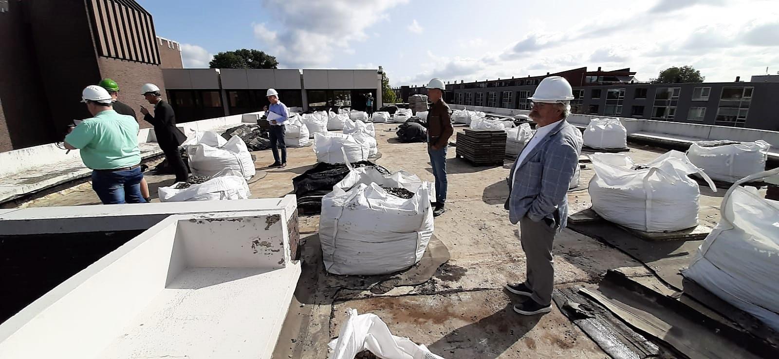 Op het dak van het stadskantoor staan bigbags met grint klaar. Ze gaan verder als ballastmateriaal  voor het spoor. Wethouder Cees Lok (re) kijkt toe.