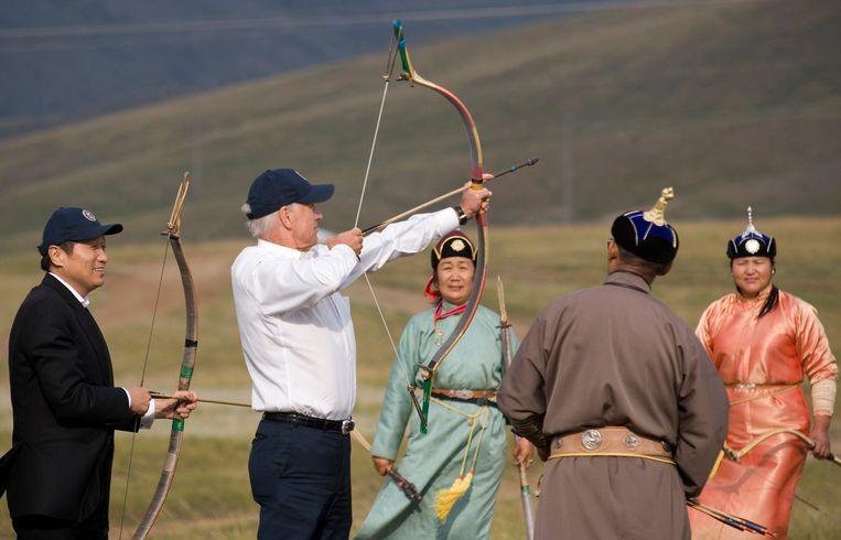 Joe Biden (tweede van links) in de weer met pijl en boog tijdens een bezoek aan Mongolië in 2011.  Beeld REUTERS