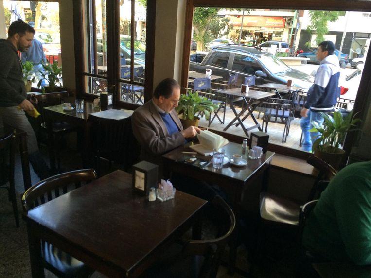 Een nette heer leest een boek in Voulez Bar, in de wijk waar Del Potro woont in Buenos Aires. Beeld Pieter Hotse Smit