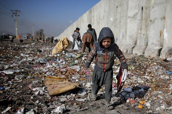 Een Afghaans kind zoekt op een vuilnisbelt naar plastic. Beeld uit 2019.
