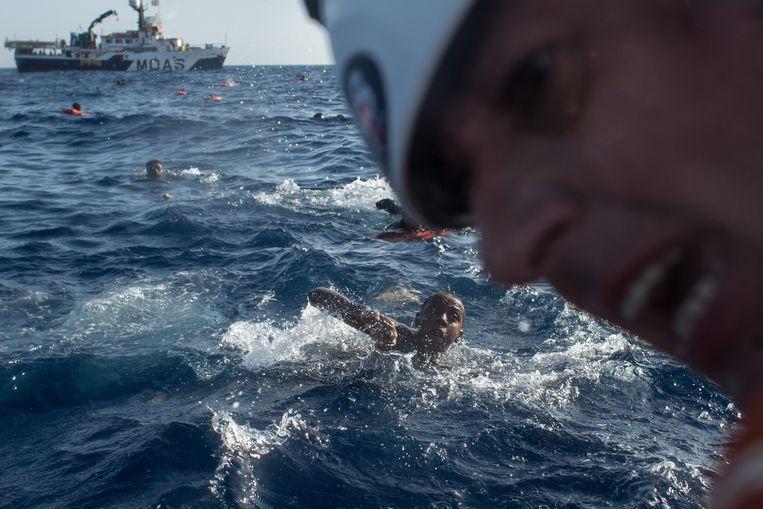 Drenkelingen zwemmen naar een reddingsboot van MOAS. Beeld Getty Images