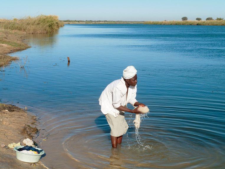 Een vrouw doet de was in de nog schone Okavangorivier. Beeld Hollandse Hoogte / Mary Evans Picture