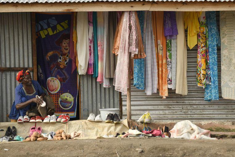 Aan het strand van Mbita, aan het Victoriameer, biedt een verkoopster tweedehands kleding aan.  Beeld AFP