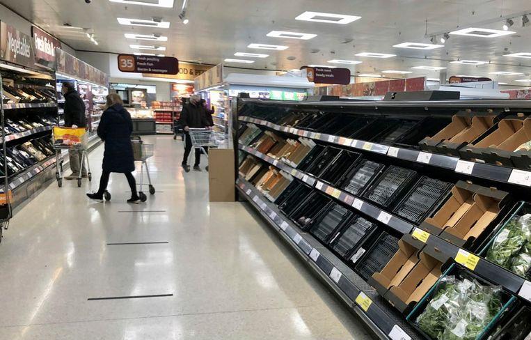 Lege rekken in een filiaal van de supermarktketen Sainsbury's in Belfast in Noord-Ierland.  Beeld AP