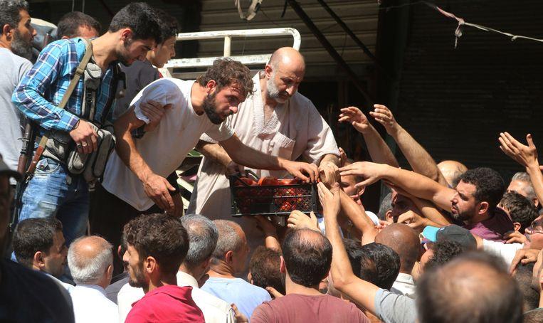 Inwoners van Aleppo proberen voedsel te kopen dat is binnengebracht door de humanitaire corridor in de stad. Beeld REUTERS