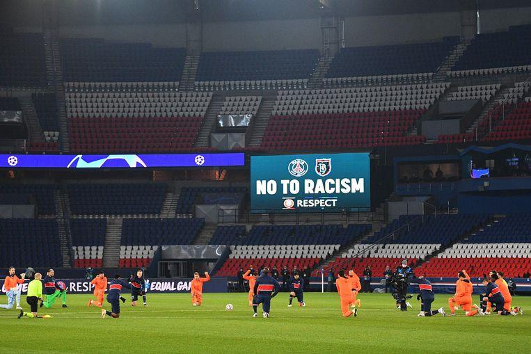 De spelers van PSG en Basaksehir knielen voor hun Champions League-match in Parijs. Beeld AFP