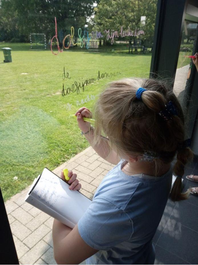 Gedichtjes van de kinderen kregen een plaats op de ramen van de school.