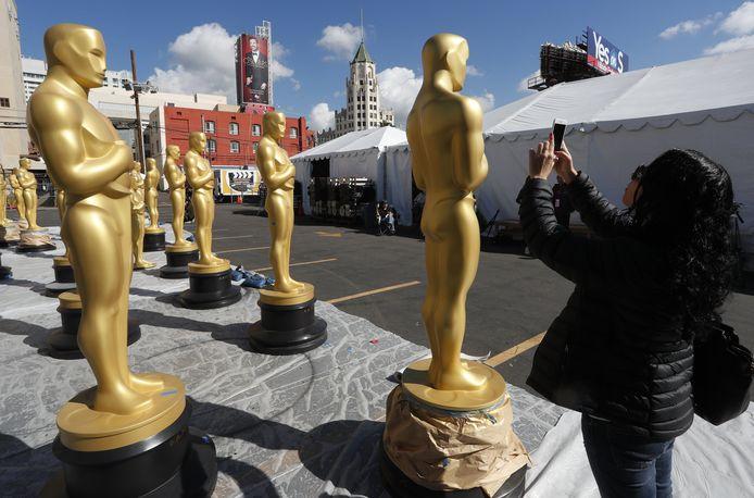 Een vrouw neemt een foto van levensgrote Oscar-beelden in Los Angeles.