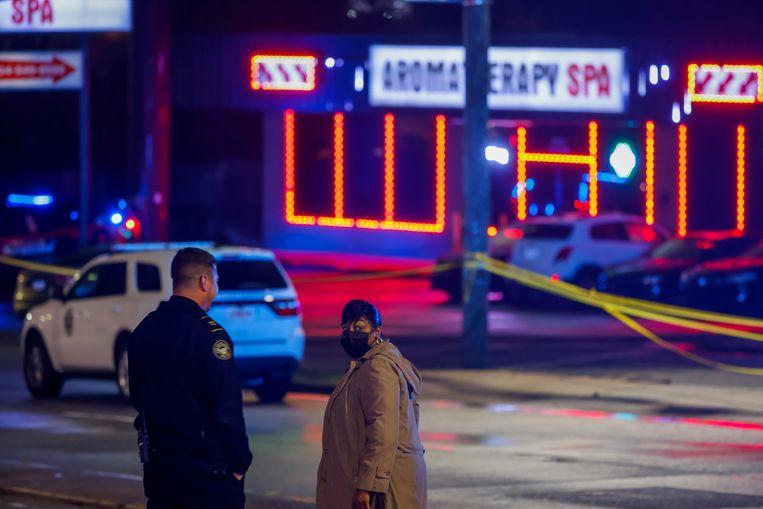 Een politieagent praat met een omstander bij een van de massagesalons waar de schutter het vuur opende. Beeld EPA