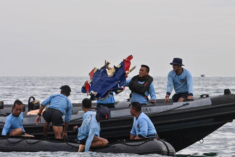 Indonesische marineduikers met een wrakstuk van vlucht SJ182. Beeld AFP