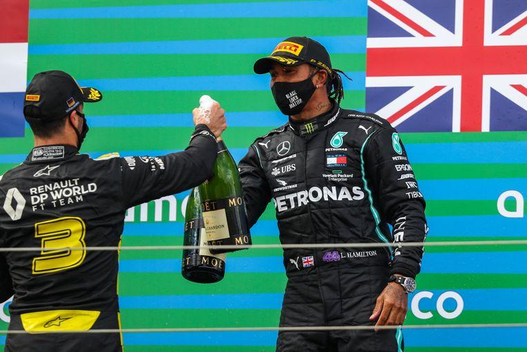Daniel Ricciardo (links) en Lewis Hamilton klinken met champagneflessen op het podium in Duitsland. Beeld Photo News